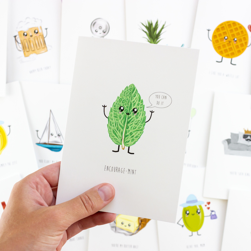 A hand holding a funny card depicting a mint leaf with a cartoon face. In the backgound are several more greeting cards that are slightly out of focus.