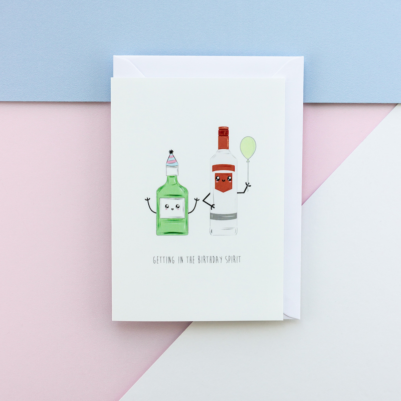A comical greeting card depicting a bottle of gin and a bottle of vodka. The shorter gin bottle is wearing a party hat and the taller vodka bottle is holding a balloon. Both bottles have a cartoon style face.