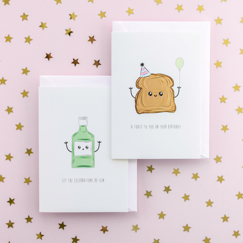 Two jocular greeting cards, one of a bottle of gin and one of a piece of toast. Both have funny faces and arms. The toast has a party hat and is holding a balloon.