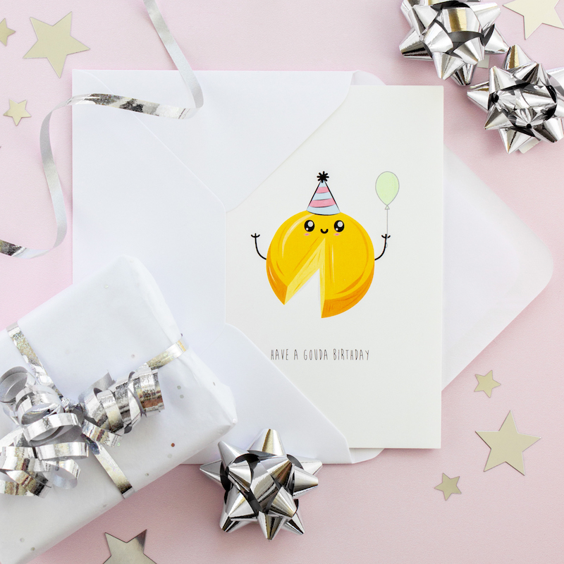 Witty greeting card with an illustration of a piece of gauda cheese with a cartoon style face, wearing a party hat and holding a green balloon.