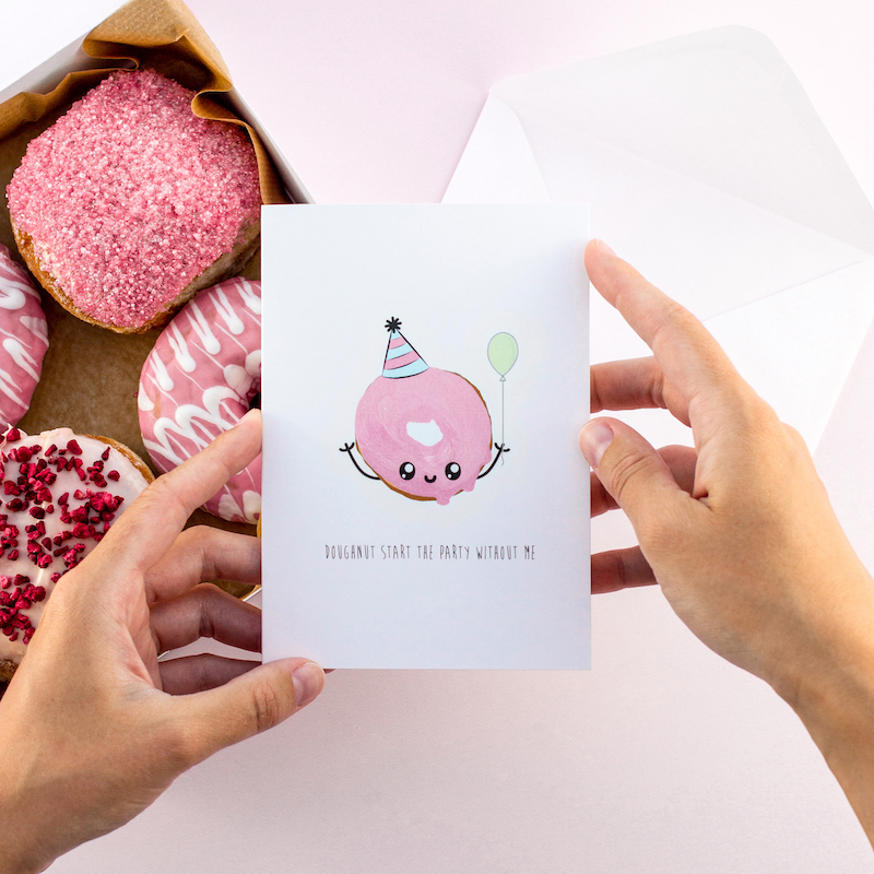 A box of delicious looking doughnuts with one of our greeting cards being held just above the box. On the greeting card is an illustration of a doughnut with pink icing. It has an amusing face and is wearing a party hat as well as holding a balloon.