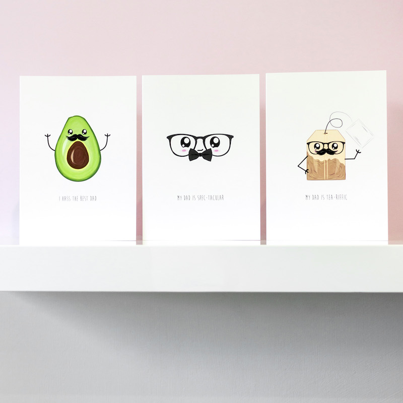 Three funny greeting cards in a row on a shelf, one of an avocado with a face and moustache, the second a pair of glasses with big eyes and a bow tie. The third is a tea bag with a face and moustache.