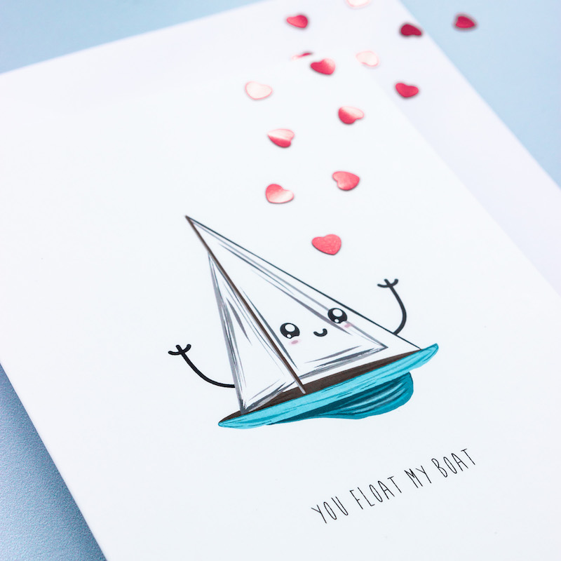 A jocular greeting card of a sailing boat with a blue hull and wite sails. The sails have a cartoon face and arms uplifted in an expression of joy.