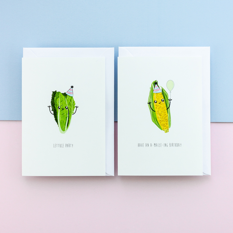 Two funny greeting cards, one of a lettuce and one of maize or corn. Both have funny faces and arms. The lettuce has a party hat and the maize is holding a balloon.