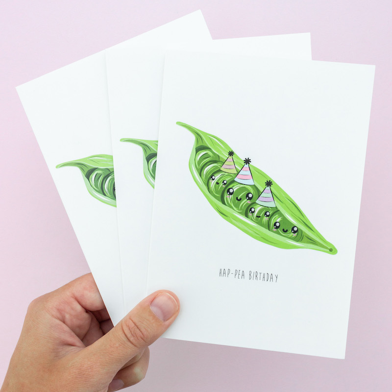 A selection of three witty greeting cards (all the same) depicting an open pea pod with six peas snuggly 'sitting' inside. Three of the peas have party hats and funny faces.