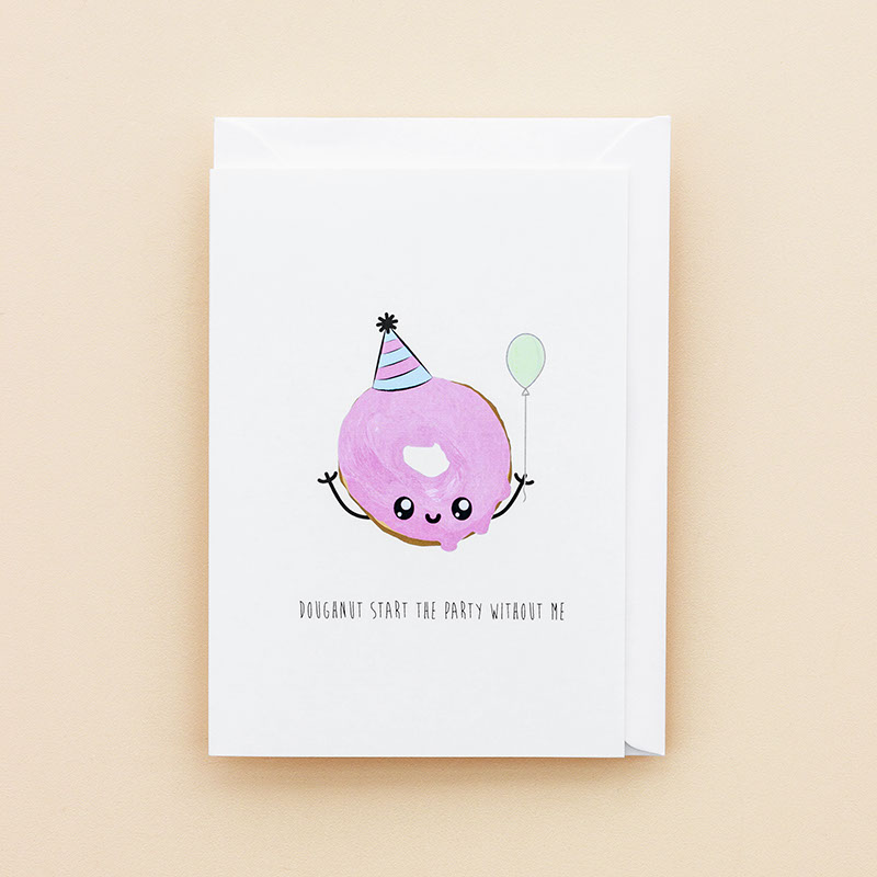 Witty greeting card with an illustration of a doughnut covered in pink icing with a cartoon style face, wearing a party hat and holding a green balloon. Used as a link to the celebration/party cards page.