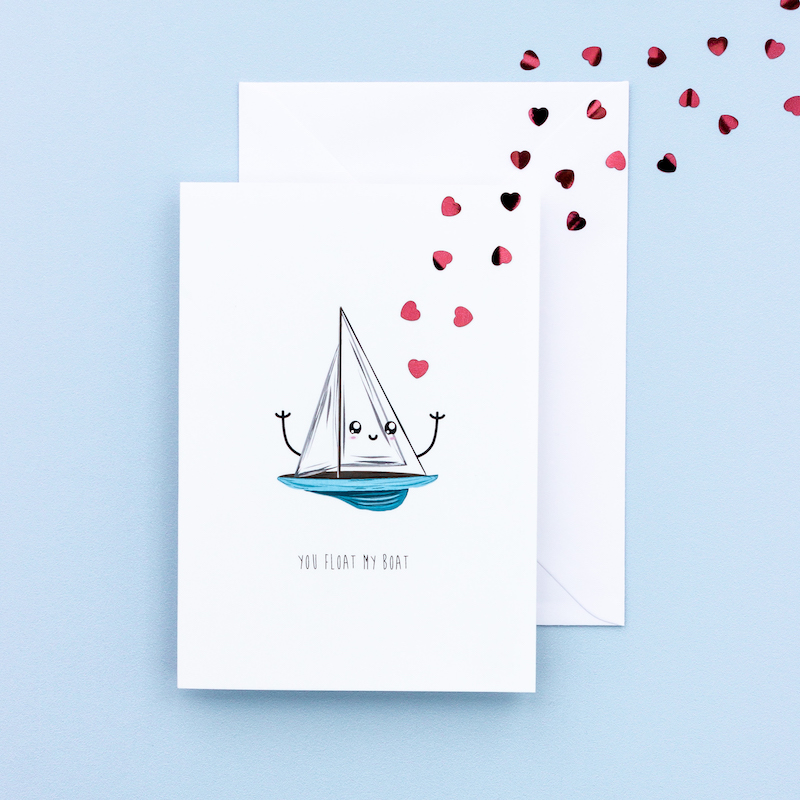 Jocular greeting card with an illustration of a sailong boat that has a blue hull and white sails with a cartoon style face. Used as a link to the anniversary/valentine cards page.